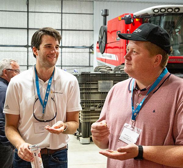 two individuals examining barley grains